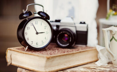 Clock is prominently placed upon a book and is to the left of an old fashioned camera.