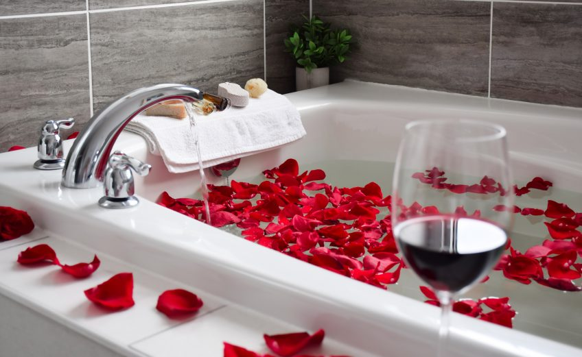 White tub with red rose petals. A towel rests on the side and water is running from the faucet into the tub. A red glass of wine is in the corner of the photo.